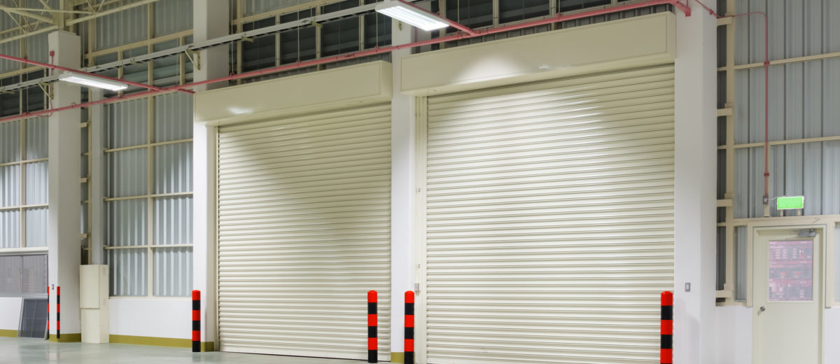Interior of factory with shutter door, night time.